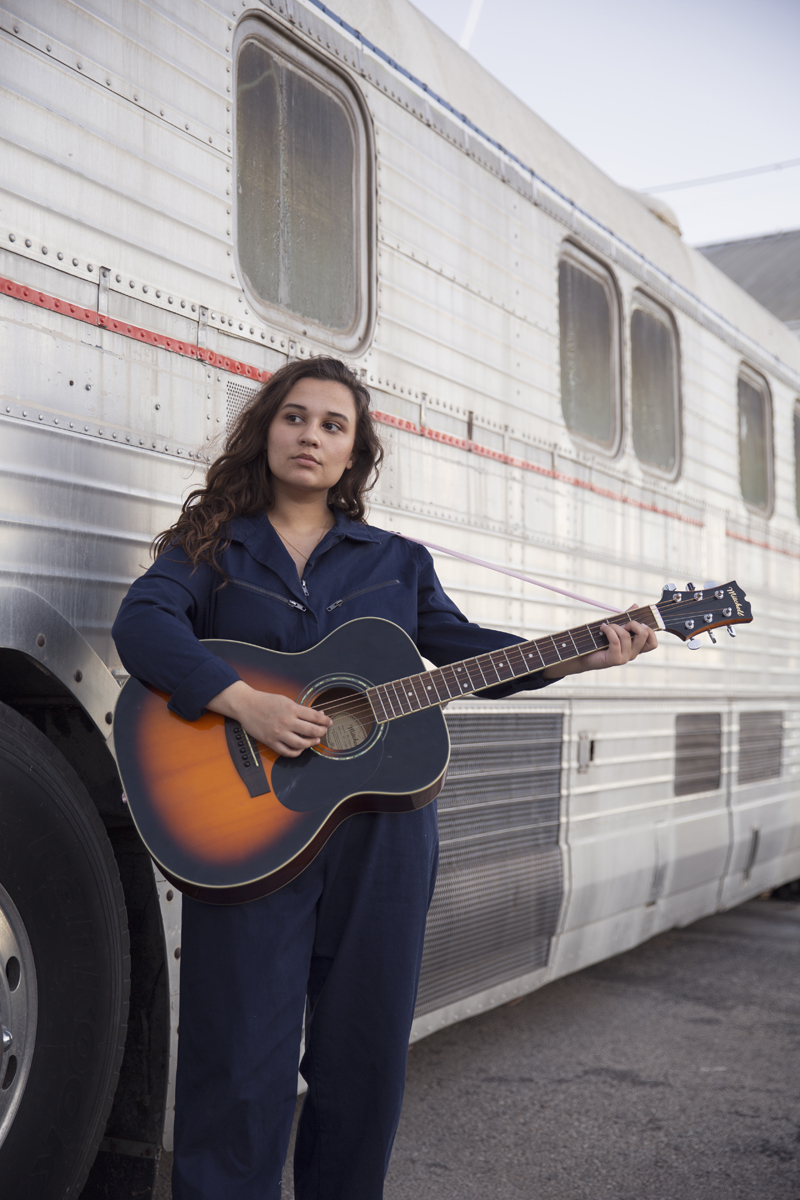 Mik Sullivan - Playing Guitar in front a tour bus