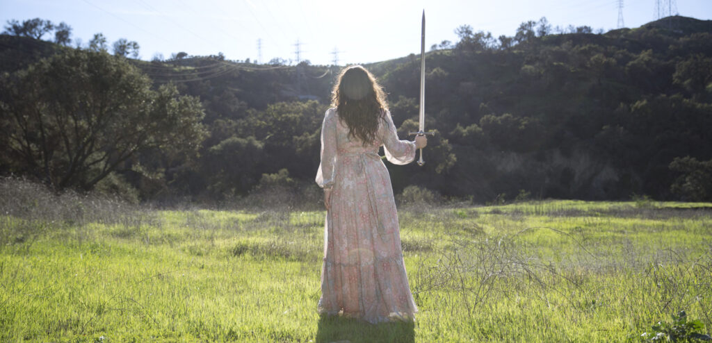 Mik Sullivan standing in a field facing mountains holding a sword wearing a flowy pink dress