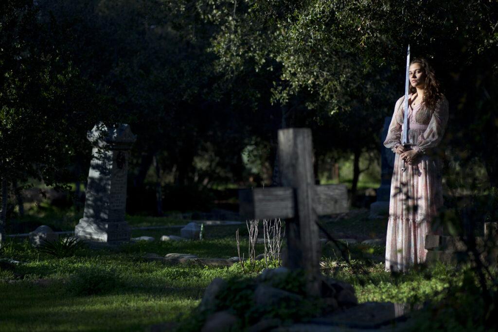Mik Sullivan in a Dark Graveyard with a sword in a flowy dress